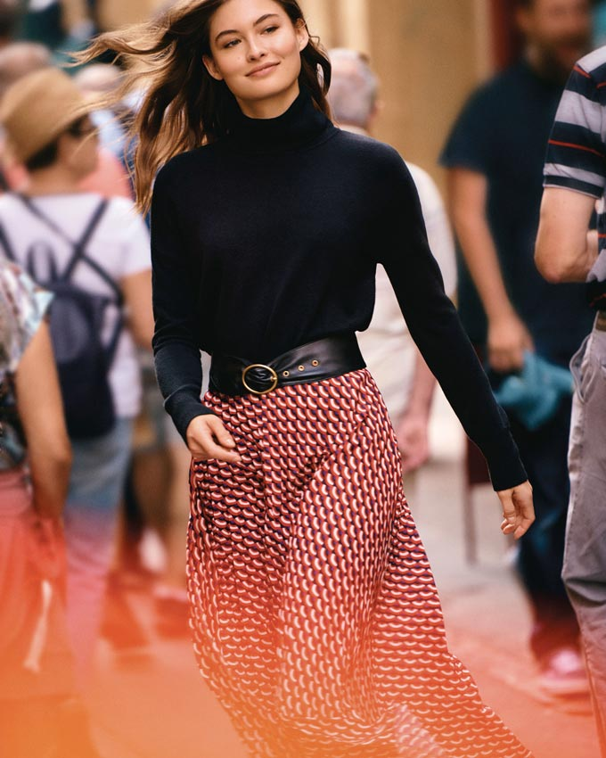 I love the outfit, a flowy soft print skirt paired with a black turtleneck and black waist belt. She's filled with confidence as she makes her way through the street crowds. Image by Next.