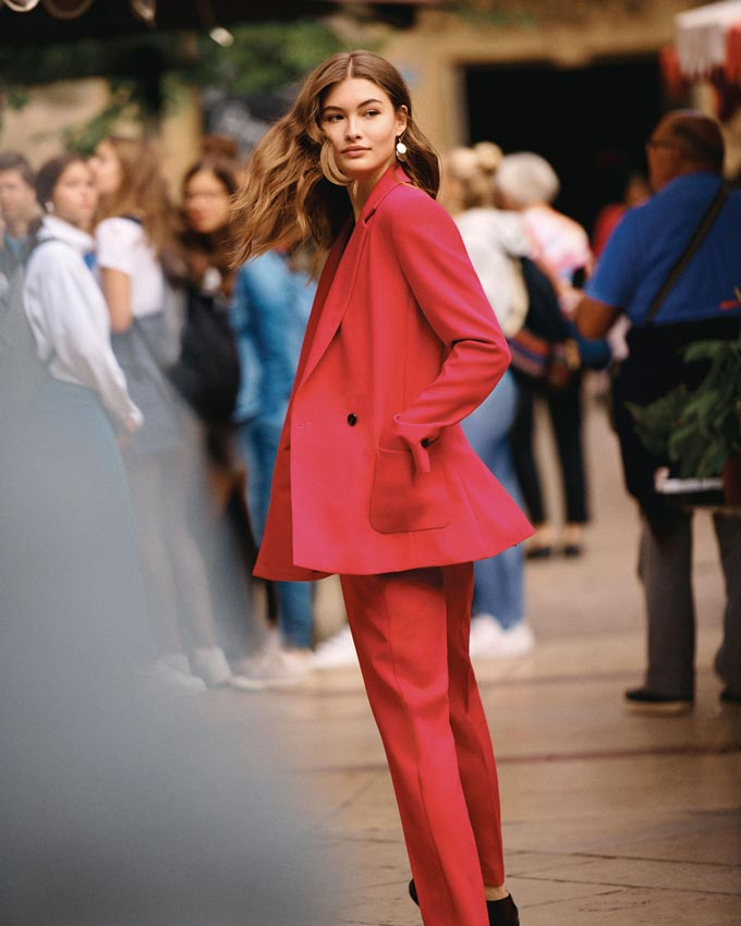 A muted red pant suit is not a bad idea now that spring is coming as worn by this young woman. Image by Next.