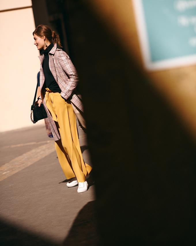 She looks so fine in her mustard high waist pants, black top and plaid overcoat. She's paired them with some white kicks and off she goes. Image by Next.