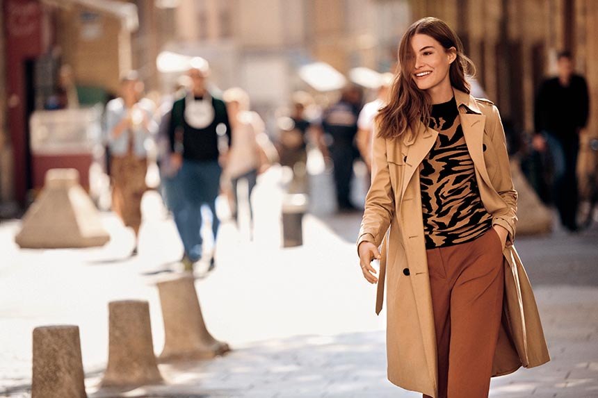 A woman dressed in camel and coffee colors always looks chic, just like her. Her print blouse spices it all up just a bit. Image by Next.