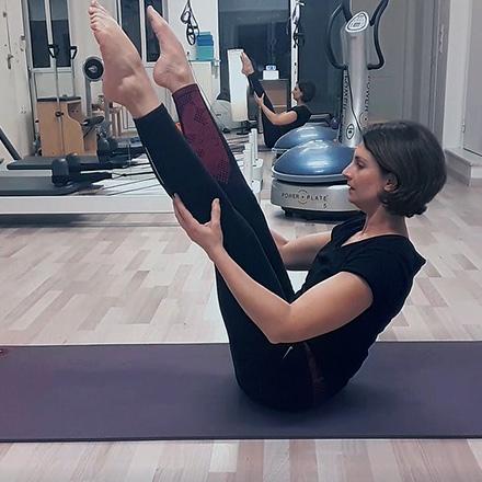 Ifiyenia at the open leg rocker position from a Pilates mat exercise.
