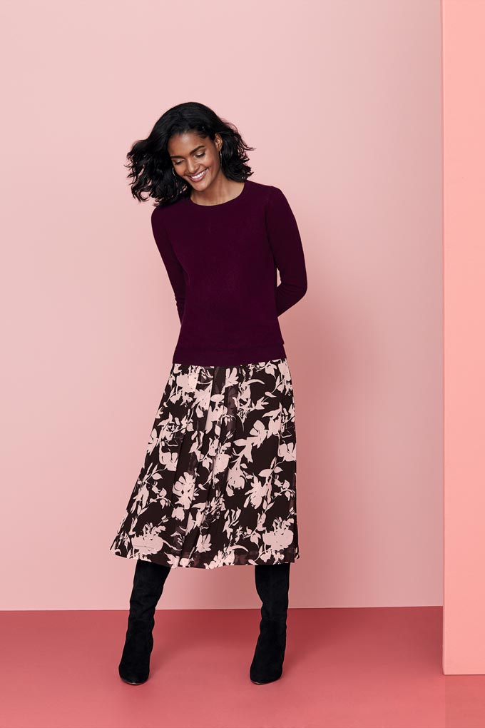 A lovely print skirt paired with a casual dark top and color coordinated knee high boots always looks really feminine. Image by Pure Collection.