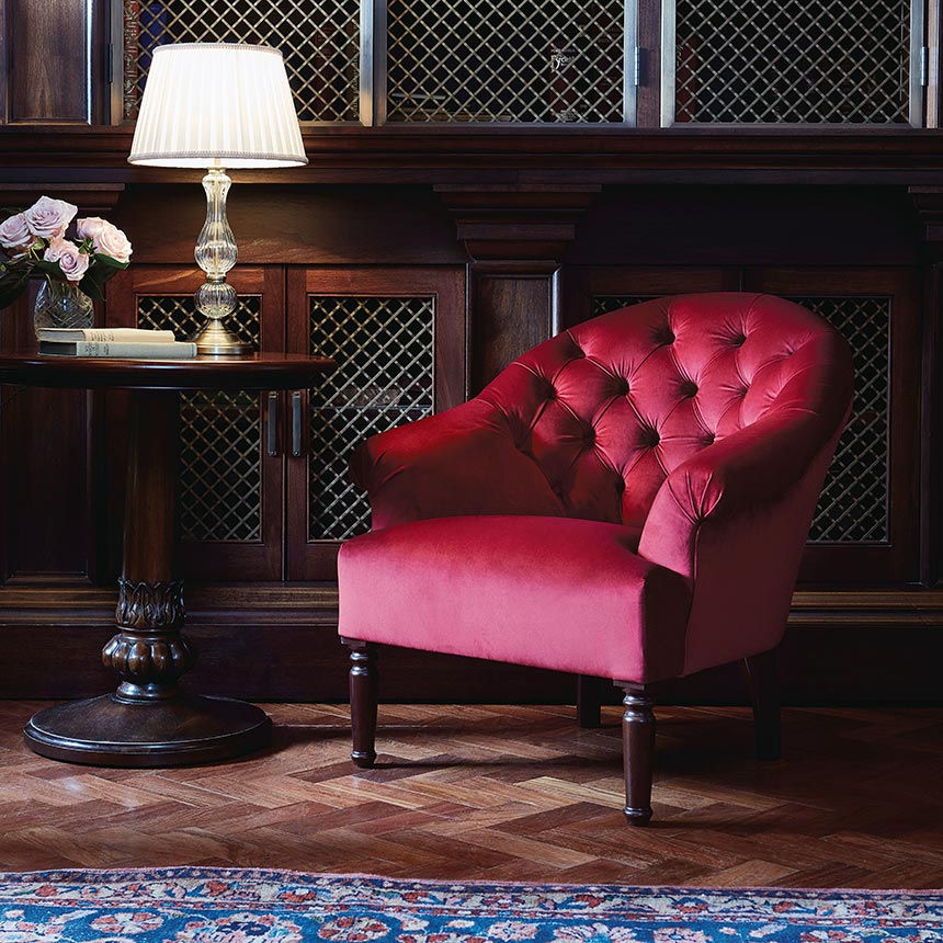 A beautiful vignette with a red velvet armchair, a wooden side table. Lovely! Image by Soho House.