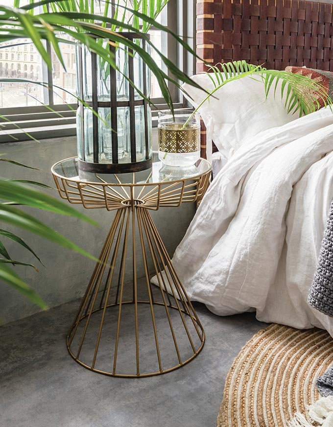 Love this the Gatsby birdcage side table used as a nightstand besides a bed with a weaved leather headboard. Image by Cuckooland.