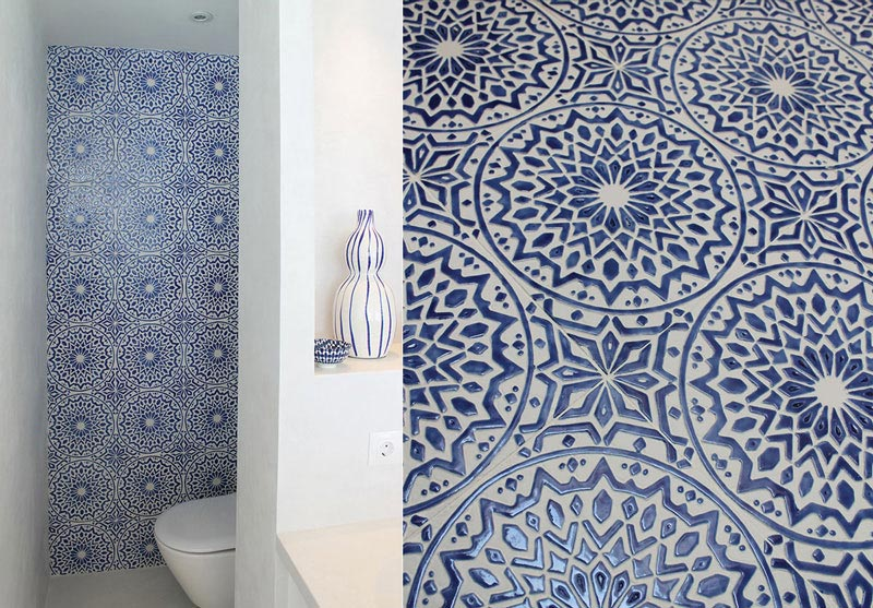 A white bathroom with an accent wall of blue and white decorative tiles. Image by G. Vega.