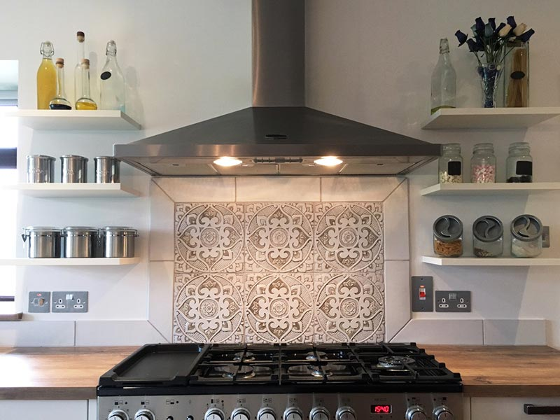 Detail of a kitchen backsplash with decorative tiles behind the cooker. Image by G. Vega.