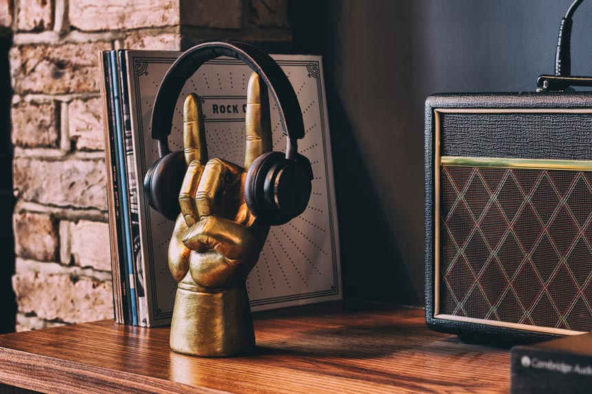 A brass hand as a headphone stand on a bookshelf. Cool idea. Image by Animi Causa.