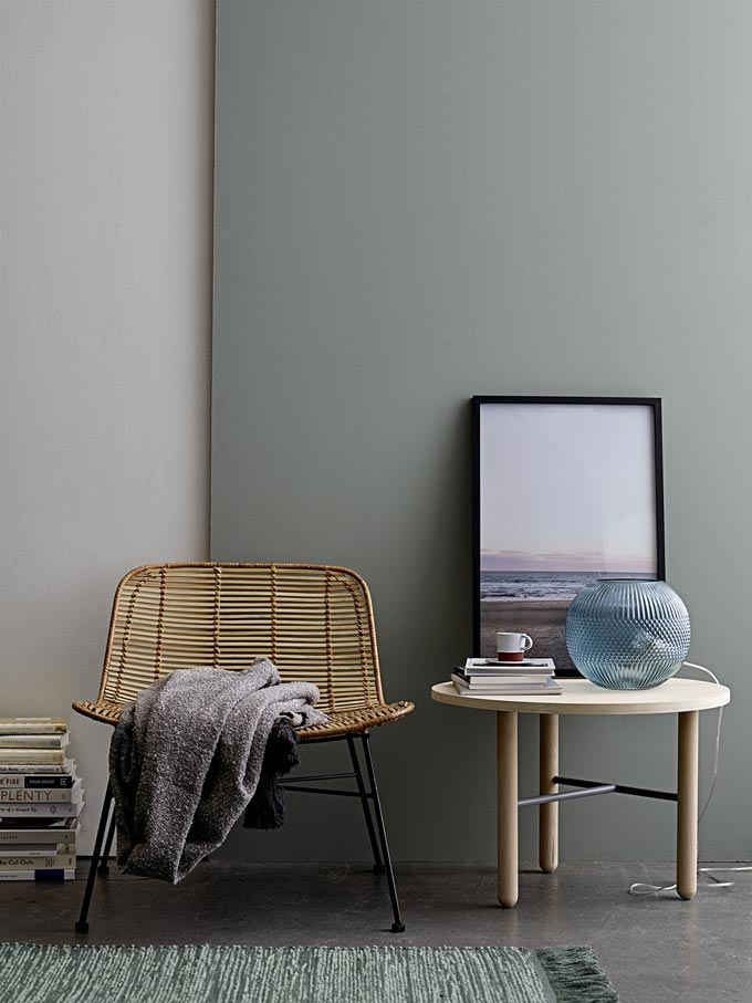 A minimal Scandi inspired vignette with a Dom by Bloomingville rattan chair next to a round side table decorated with books, a lamp and an art frame. Image by Lagoon.