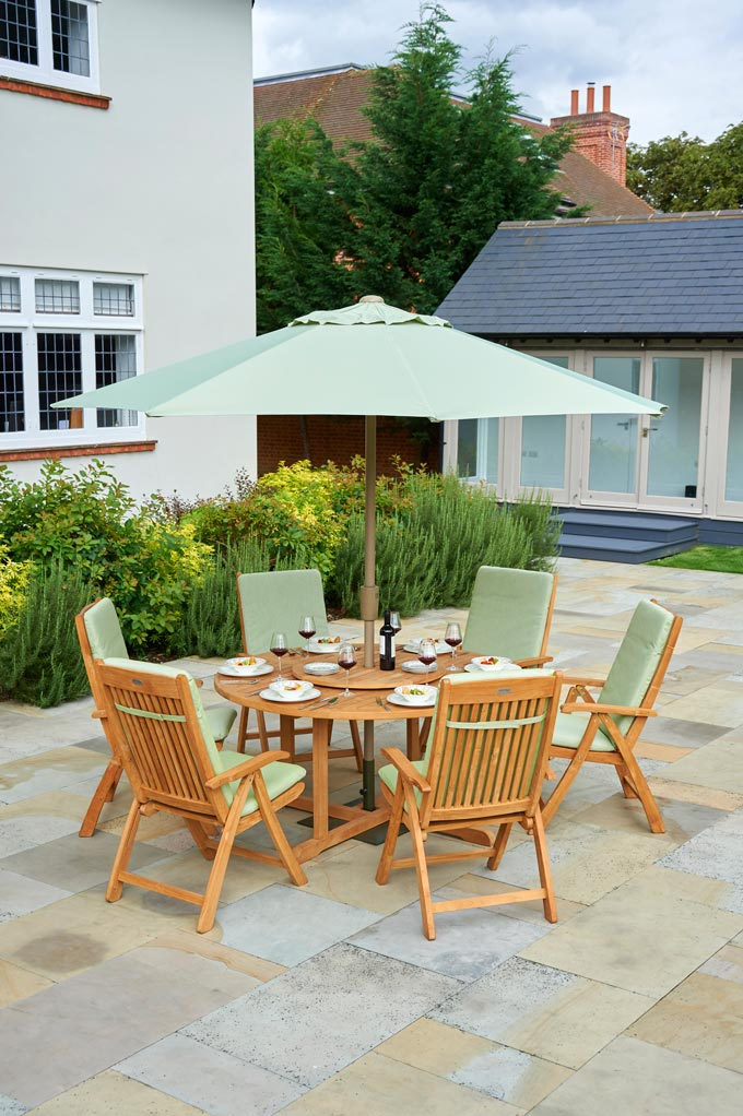 I love this minty outdoor furniture set with a teak round table, sun umbrella, and lazy Susan chairs. Image by This gorgeous set is contemporary with a traditional feel Bridgman Garden.