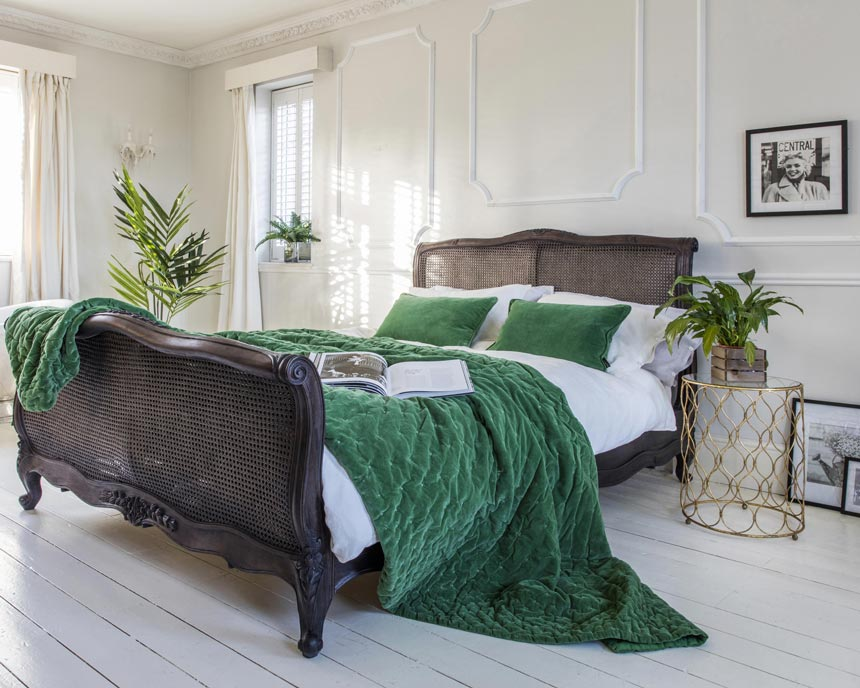 Striking elegance! A beautiful bedroom with a vintage looking bed with cane inserts at the headboard and footboard. Image by The French Bedroom Co.