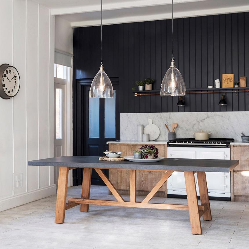 A large dining table with a concrete table top looking real good in this kitchen with a black wall panel wall in the background. The table is from Idyll Home.