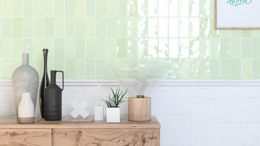 Part of a wall has been tiled with beautiful glossy soft mint green tiles. The sideboard in front of it gives it a bit of an organic and rustic vibe. Image by WOW Design.