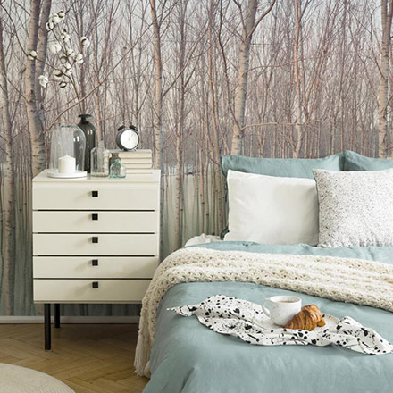 A beautiful bedroom with a wall mural of a forest as an accent and a bed with mint color bedding looking soft and cozy. Image by Pixers.