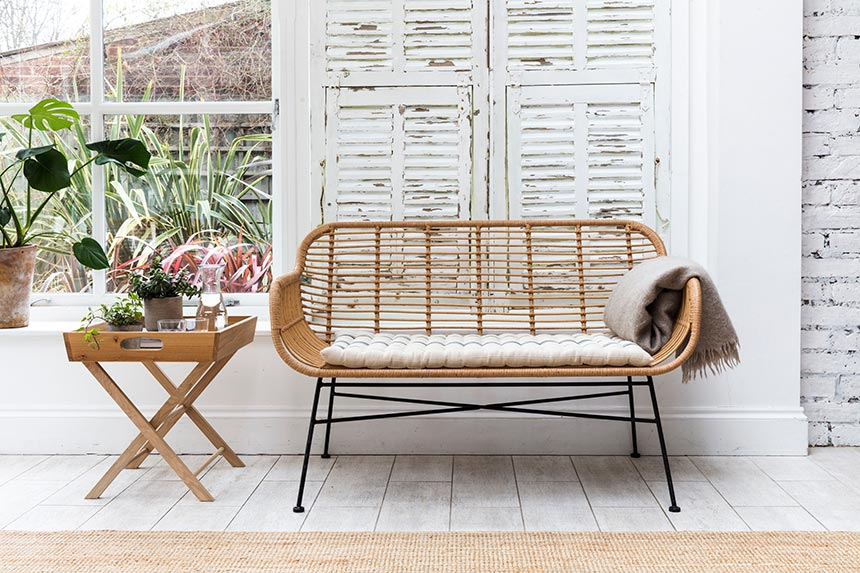 This looks so French or not? A rattan bench with a seat pad and thin, steel legs looking so elegant in front of a vintage looking white window shutter. Image by Garden Trading.
