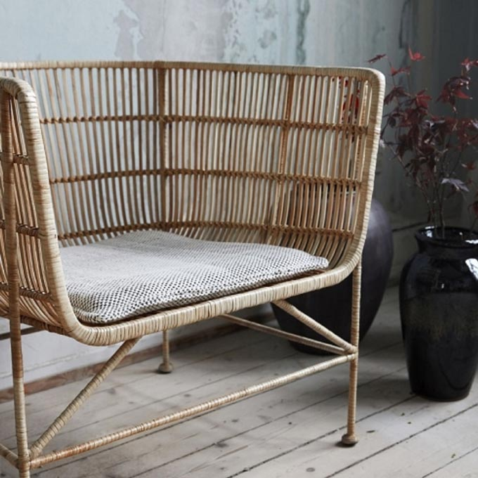 A cozy rattan curved back armchair, Coon by House Doctor. Image by Lagoon.