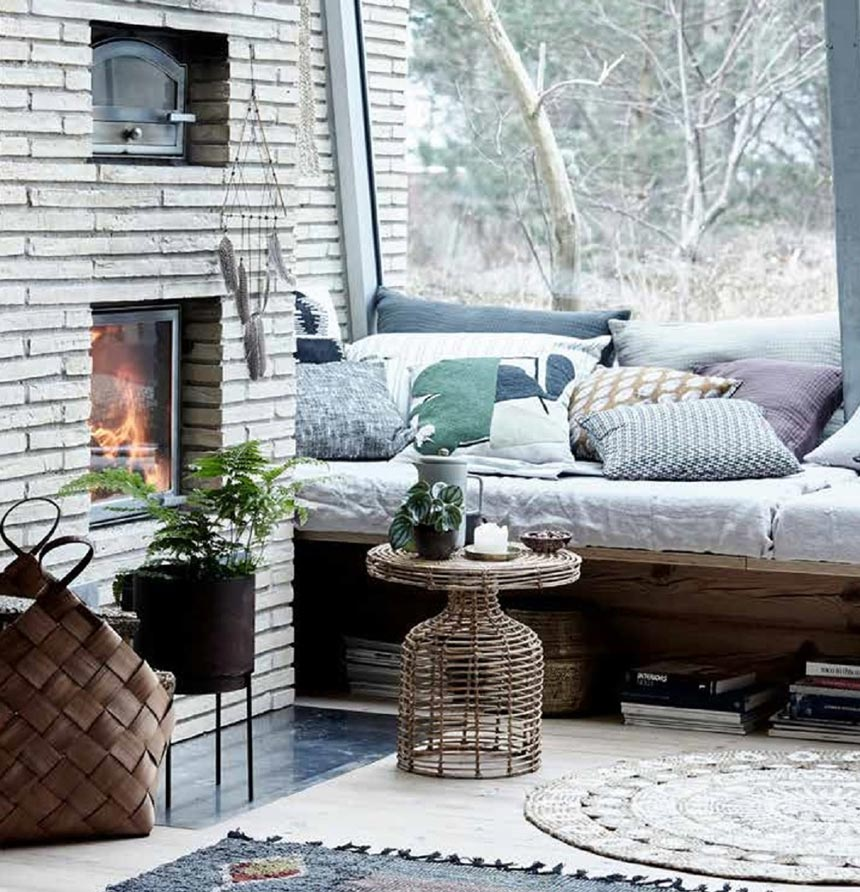 A living room with a fireplace and a large window on the side looks so charming with a real hygge feeling to it. The round rattan side table by House Doctor is the detail that adds a vintage charm to it all. Image by Lagoon.