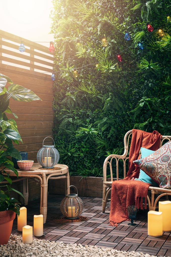Candles and rattan lanterns add such warmth even in an outdoor space. An outdoor vignette with a rattan sofa and side table and blanket thick green foliage in the background looks a lot like a place I want to have for myself. Image by ©Lights4fun.