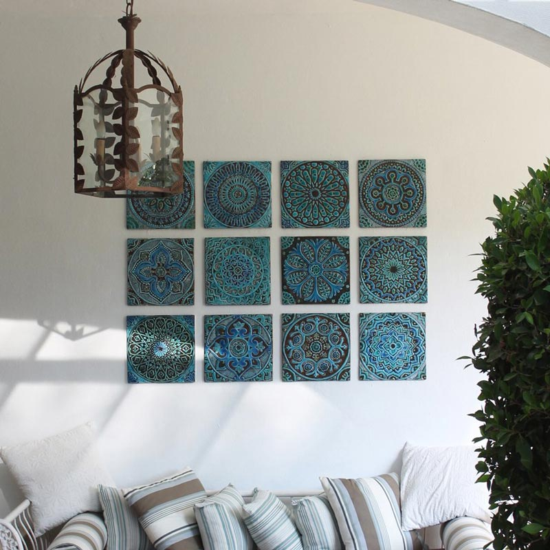 A covered roof outdoor space with a boho vibe and a sofa against a wall that features three rows of decorative handmade turquoise tiles. Image by G. Vega.