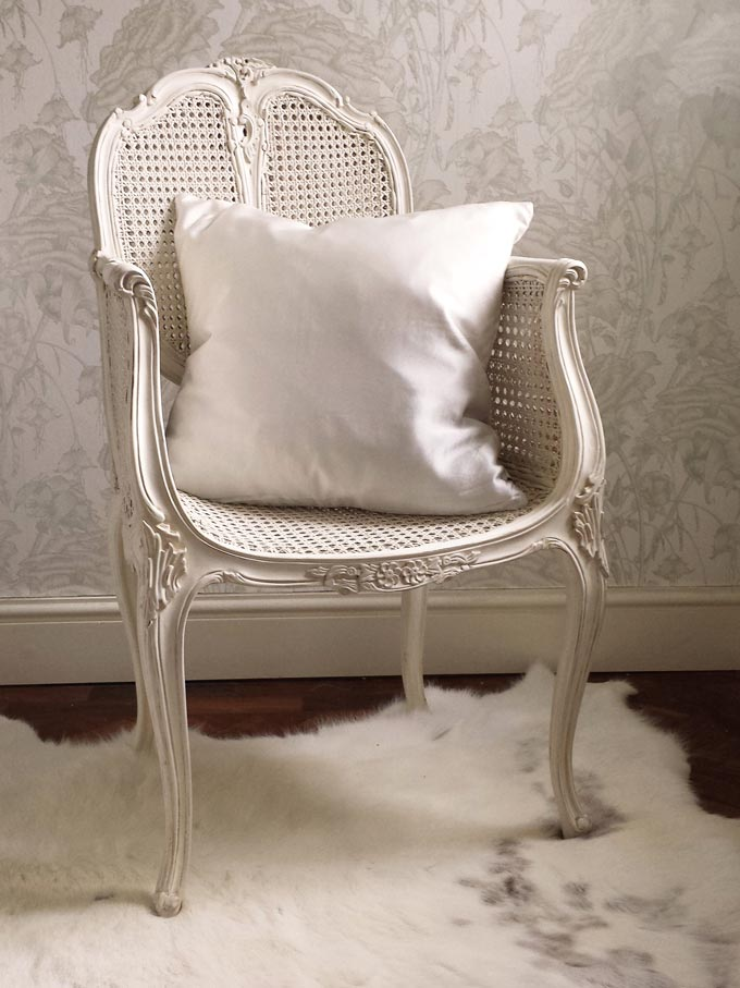 How beautiful is this rattan bedroom chair with an off-white mahogany frame and a flair of a colonial style. Image by The French Bedroom Co.