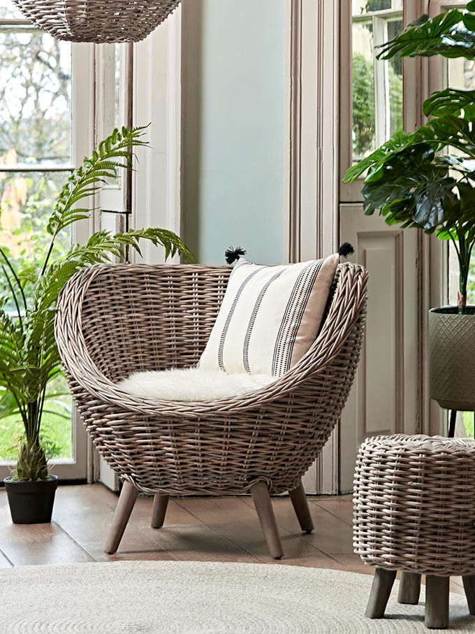 A vignette with a rattan tub chair and simple seating looking elegant. Image by Cox & Cox.