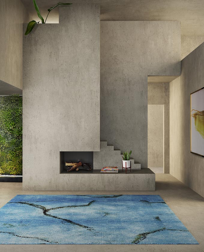 A stunning space with bare concrete walls, a contemporary concrete fireplace and an amazing blue handmade rug in front of it from Rug'Society. Wow!