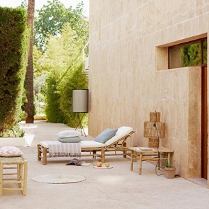 An elegant outdoor setup with a rattan lounge chair and furniture looking lovely with a garden in the background. The suspension lampshade made of rattan designed by Tine K Home is that little detail that makes a difference. Image by Nedgis.