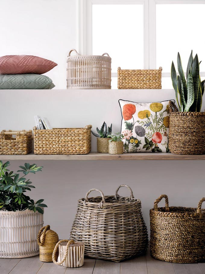 Open shelves stacked with rattan baskets, plants, cushion and decorative pillows. It has a bohemian flair to it but in a very refined way. Image by El Corte Inglés Decoración.