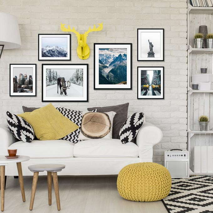 A contemporary setting with a white sofa, mustard accents, an art gallery wall with prints on a white brick accent wall besides a white bookcase. Image by Abstract House.