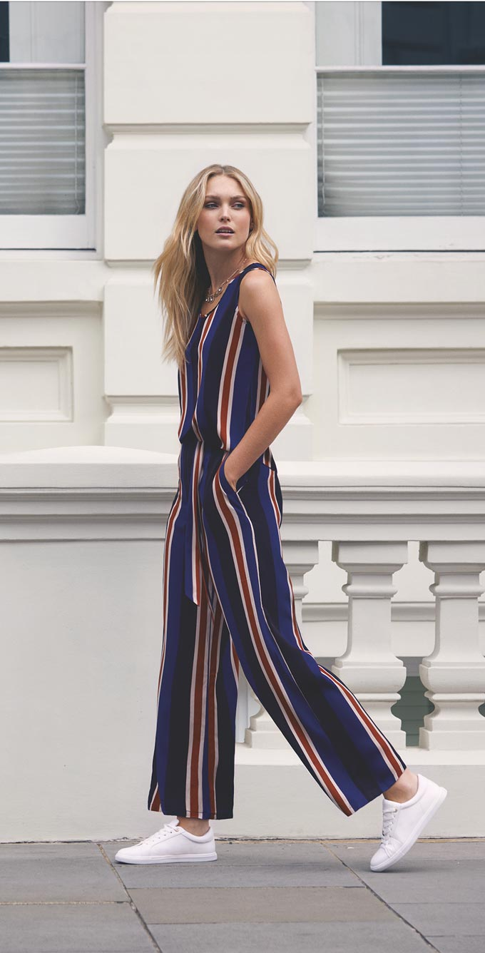 A striped sleeveless jumpsuit paired with some white trainers is a really elegant casual outfit. Image by Apricot.