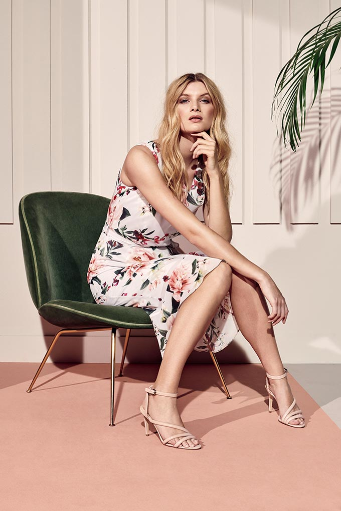 A beautiful floral print sleeveless dress that's perfect from dawn till dusk. In this case she paired it with some beige sandals. Image by Dorothy Perkins.