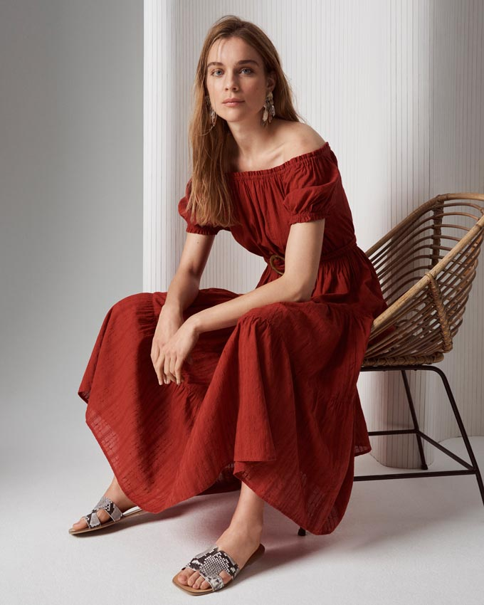 A beautiful off the shoulder maxi dress in a deep terracotta color paired with snake print flat sandals. Image by Marks & Spencer.