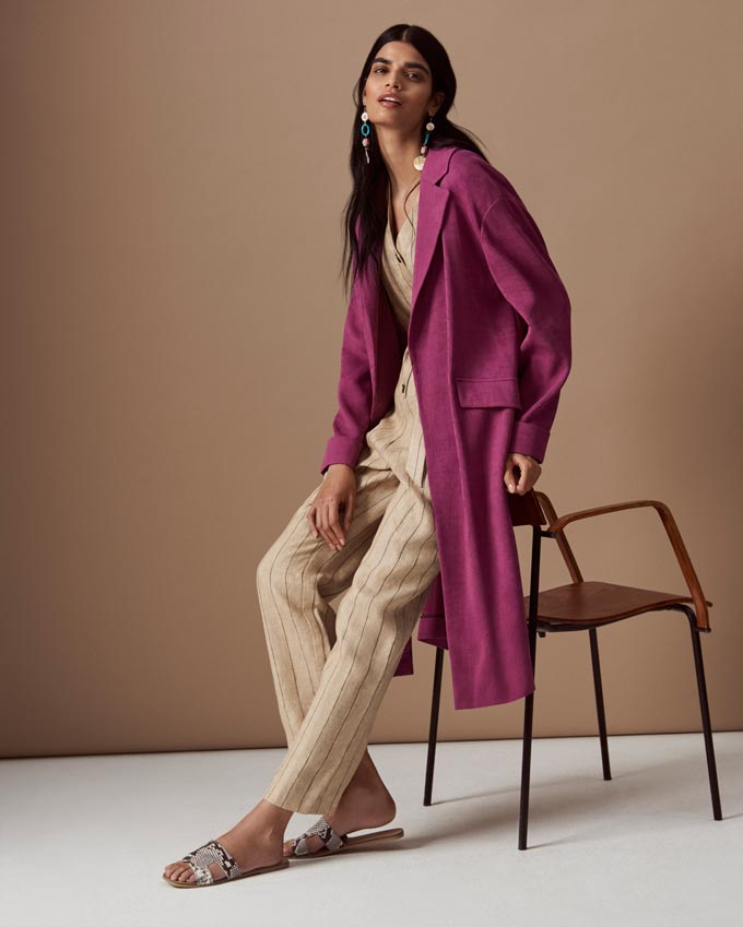 A beige jumpsuit with a mauve coat over it looking stunning. Image by Marks & Spencer.