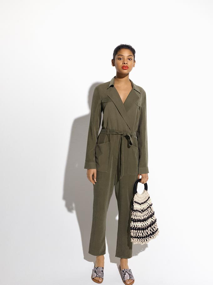 A khaki long sleeve jumpsuit is timeless. In this image it is paired with a striped blue and white straw bag. Image by Miss Selfridge.