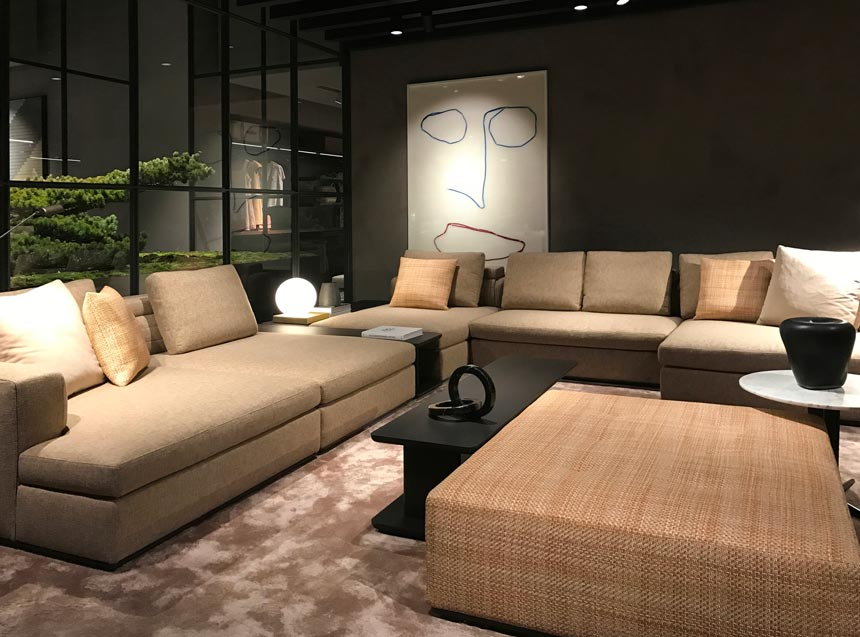 View of a contemporary living space with large comfy beige sofas from the Molteni stand at the imm Cologne 2019 fair.