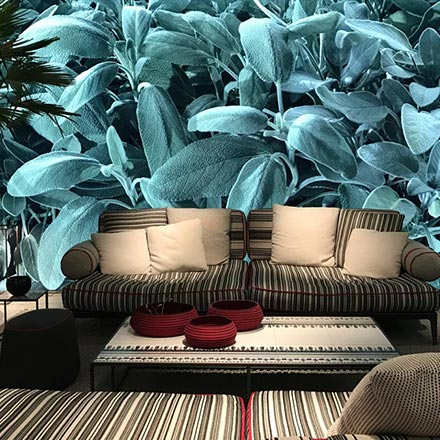 View of a stunning living space with a magnified blue green leafy accent wall as a background to a pattern print sofa. This image is from the stand of Poliform at the imm Cologne 2019 fair.