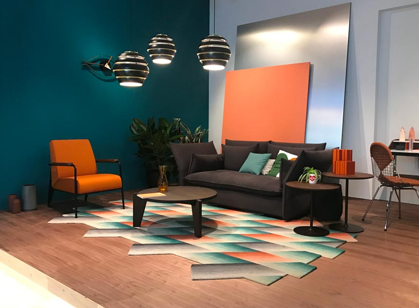 A contemporary living space with a dark sofa and an orange like armchair besides it. One of walls is in a deep teal color making an excellent backdrop for the armchair. This is part of the stand from Vitra at the imm Cologne 2019 fair.