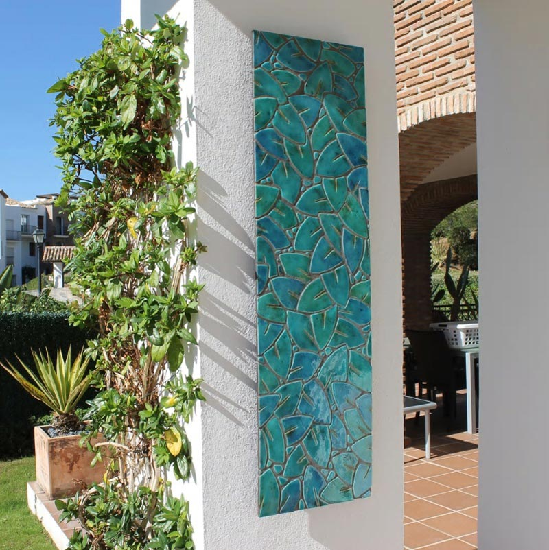 A vertical wall installation made of turquoise tiles on an outdoor house pillar. Image by G. Vega.