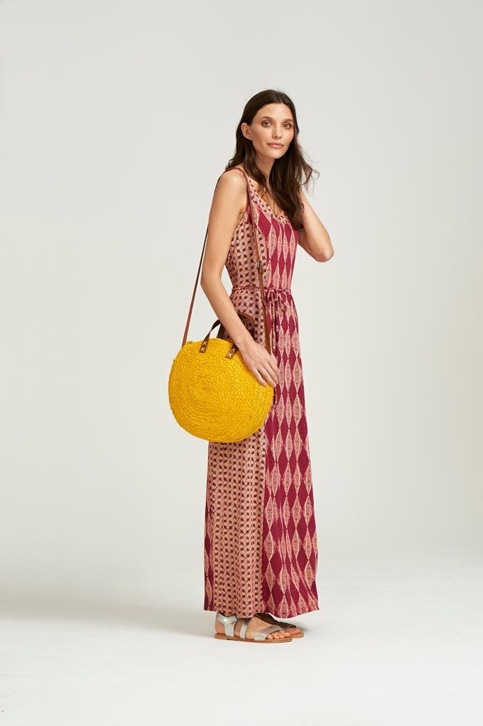 A maxi print sleeveless dress paired with a mimosa yellow, round straw bag. Image by Whitestuff.