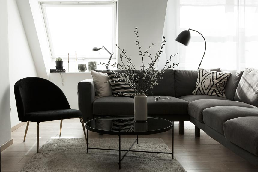 A contemporary living room with a modular grey sofa, a round black coffee table and the velvet upholstered Heather lounge chair. Image by Cult Furniture.