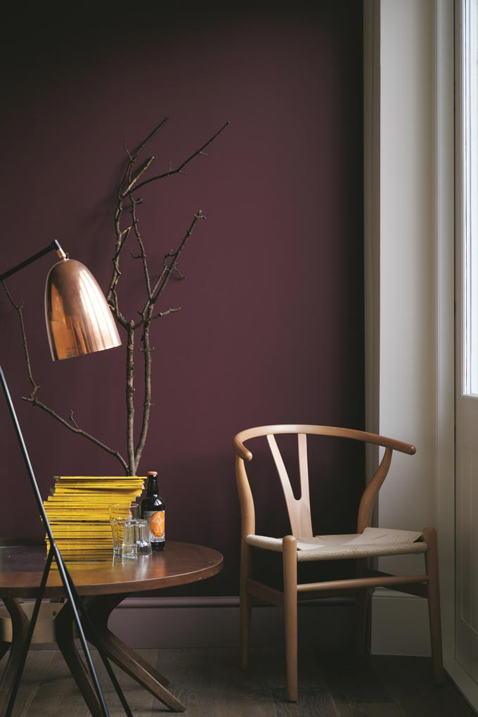 A vignette by a window with an amazing background saturated color on the wall from Farrow and Ball, highlighting a wishbone chair and the round side table perfectly. Image by Farrow and Ball.