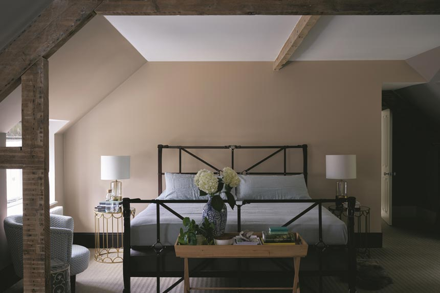 A beautiful bedroom with a warm and neutral color palette looking simple but very elegant. Image by Farrow and Ball.