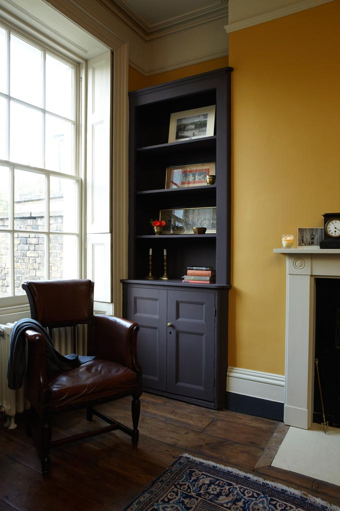 What a cozy vignette by a window with a dark built in bookcase, a fireplace and bold ochre yellow wall to contrast those rustic but sophisticated tones. Image by Farrow and Ball.