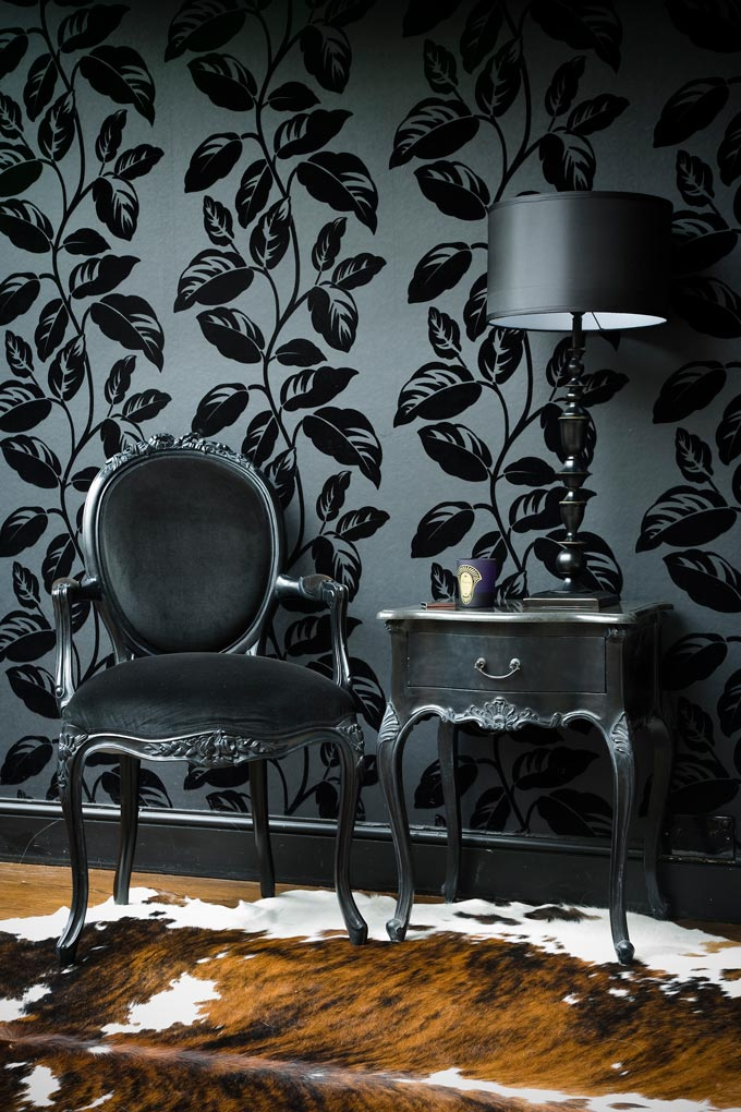 The power of color coordination is definitely overpowering this vignette with sophistication. A graphite gray background with black print leaves on a wallpapered wall act as a backdrop to a graphite grey velvet upholstered vintage inspired armchair and side table in this captivating vignette. Image: The French Bedroom Co.