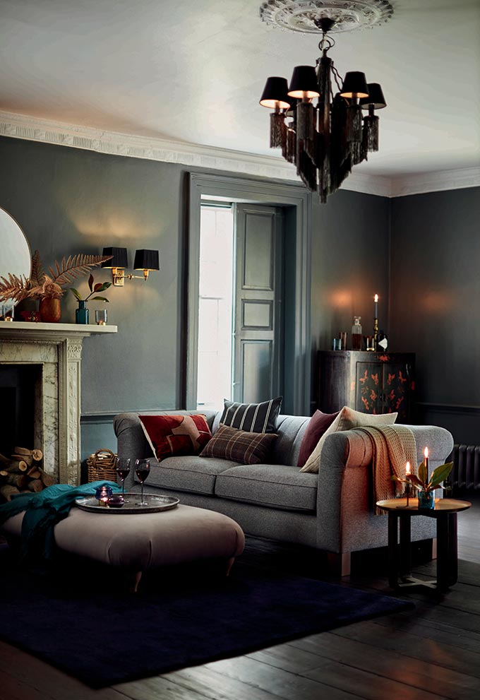 A living room in a deep blue grey saturated hue can look quite warm and inviting when the sofa is right. It's not about the fireplace, but the comfort and homey feeling it emits. Image by DFS.