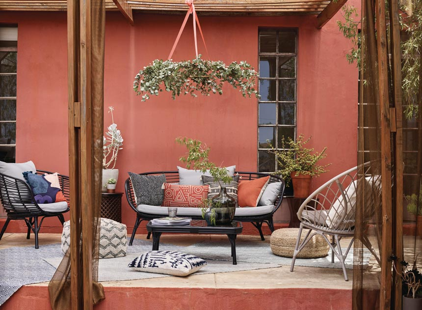 A stylish outdoor sitting space with a boho flair to it against a terracotta accent external facade. Image by John Lewis.