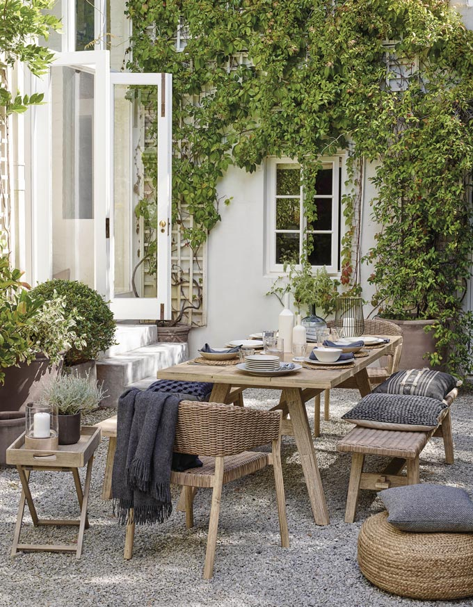 An outdoor dining space set up for entertaining with a rustic style, benches, pillows, and lots of greenery.