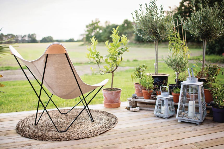 The Butterfly Chair set up outdoors next to potted plants and lanterns on a deck, overlooking a green field. Image by Nest.co.uk.