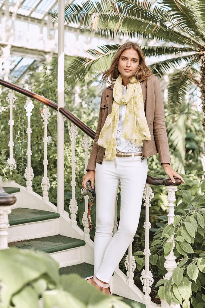 A total white outfit with white denim pants, but with a twist because of the camel biker's jacket and the yellow scarf. Image by Pure Collection.