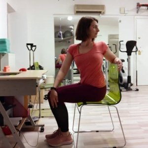 Ifiyenia Koskina while doing a stretching exercise by an office desk.