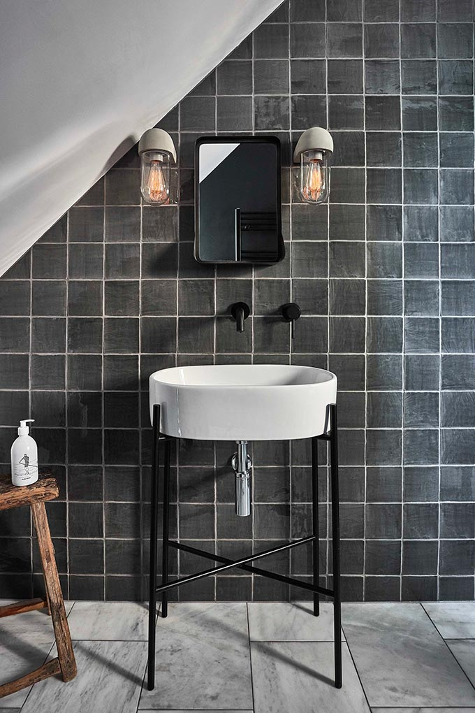 Love the white grout between the grey square tiles in this bathroom with a white washbasin on a black metal stand. The bathroom looks complete with the two sconces next to the mirror. Image by Garden Trading.